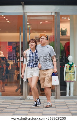 BEIJING-JULY 25, 2014. Happy young couple walks out UNIQLO outlet. UNIQLO opened its first store in China in Shanghai September 2002 and steadily expanded its network to 306 stores by August 2014.  - stock photo