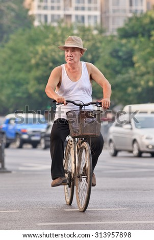 BEIJING-JULY 27, 2015. Male senior on a rusty bicycle. China's elderly population (60 years or older) is currently about 128 million, which means one in every ten people, the largest in the world. - stock photo