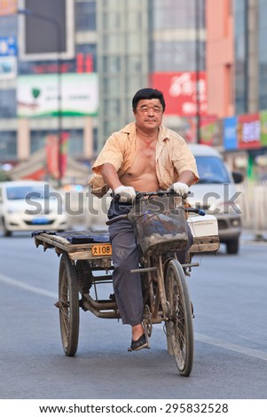 BEIJING-JULY 10, 2015. Man on rusty three wheeled freight bike. Although municipal governments try to ban them out this transportation mode is still convenient in dense, congested Chinese cities.  - stock photo