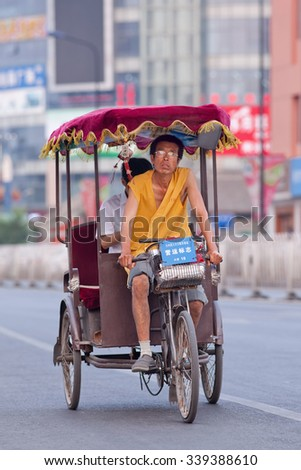 BEIJING-JULY 10, 2015. Rickshaw with a passenger. In Chinese cities rickshaws are still a popular and affordable transport mode for short distances, currently most of them are electric motorized. - stock photo