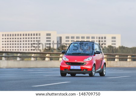 BEIJING-JULY 5. Smart Car on the road. Smart Car sales in China grew 45% in 2012 to 15,680 vehicles. Given the size of China's automobile market, it's still a niche player. Beijing, July 5, 2013. - stock photo