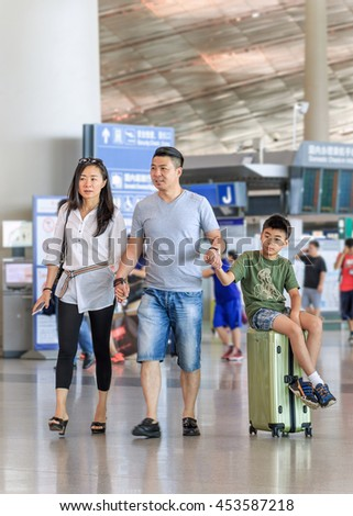 BEIJING-JULY 13, 2016. Young couple with boy on a suitcase at Beijing Capital International Airport, Terminal 3, with 986,000 square meter the second largest airport terminal building in the world.