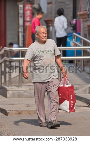 BEIJING-JUNE 9, 2015. Fashionable Old Chinese man. Elderly population (60 or older) in China is 128 million, one in every ten people, the world's largest. China will have 400 million elderly by 2050. - stock photo