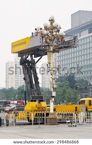 BEIJING-JUNE 16, 2015. Hydraulic lift for lantern maintenance with group of workers. The Beijing municipal government effort to clean and maintain the city center as it is the country's capital.  - stock photo