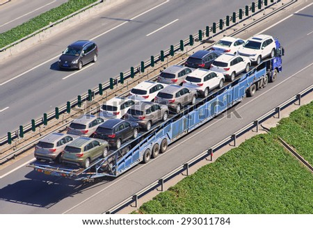 BEIJING-JUNE 30, 2015. Over sized car carrier. Although 16.5m is China's official truck length, a large number of vehicle carriers operate in open violation of the maximum length and overhang rules.  - stock photo