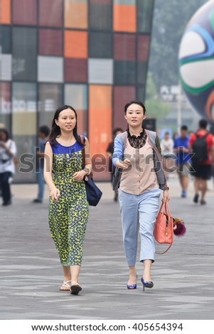 BEIJING-JUNE 25, 2014. Young women in shopping area. China's economy, boosted by middle class wealth, undergoes significant shift in consumption, driven by a new generation young prosperous consumers. - stock photo