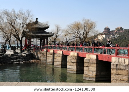 BEIJING - MAR 14:Visitors cross over a bridge at The Summer Palace in Beijing China on March 14 2009.The Summer Palace is the best preserved imperial garden in the world. - stock photo