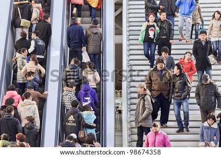 BEIJING - MARCH 10, 2012. Crowd on escalator and stairs in Beijing on March 10, 2012. With just over 1.3 billion people (1,339,724,852 as of 2010 census), China is the world's most populous country. - stock photo