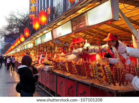 BEIJING-MARCH 17: Food vendors at the Donghuamen Night Market near Wangfujing Street on March 17, 2011 in Beijing, China. Wangfujing is a 700-year-old street.