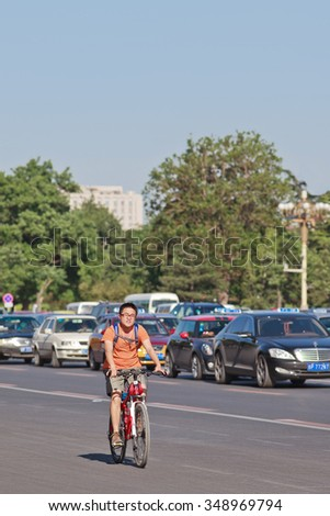 BEIJING-MAY 29, 2013. commuter on an ATB. In Beijing, with over 20 million people, daily commute is the worst of all Chinese cities, that' s why more citizens currently prefer a bicycle instead a car. - stock photo