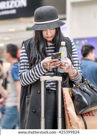 BEIJING-MAY 21, 2016. Fashionable girl with smartphone. China mobile internet market will exceed US$717 billion in 2016 with 830 million users, in 2018: 7,654 US$1,175 billion and 890 million users. - stock photo