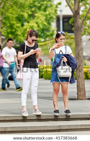 BEIJING-MAY 4, 2016. Girls busy with their smartphone. China mobile internet market will exceed US$717 billion in 2016 with 830 million users, in 2018: 7,654 US$1,175 billion and 890 million users. - stock photo