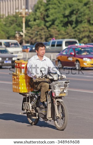 BEIJING-MAY 29, 2013. Man transports boxes on e-bike. In a decade, e-bikes in China climbed from near zero to 150 million, the largest adoption of alternative fuel vehicle in history of motorization.  - stock photo