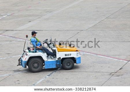 BEIJING-MAY 23. 2014. Nissan tow tractor for baggage dolly transport on Beijing Airport. Speed, efficiency, and accuracy are essential in ground handling services to minimize the turnaround time.