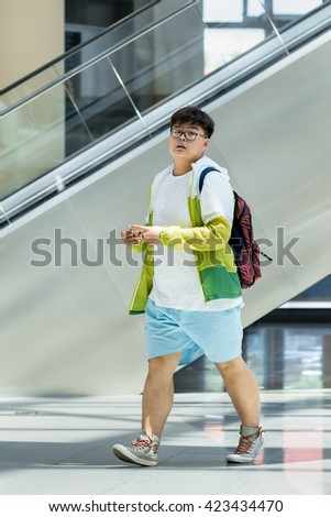 BEIJING-MAY 18, 2016. Overweight young man in shopping mall. The average waistline of Chinese urban males has gone from 63.5 cm in 1985 to 76.2 cm in 2012, growing by 20 percent over just 27 years.