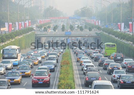 BEIJING - MAY 9: Traffic jam and smog in Beijing's Central Business District on May 9, 2012 in Beijing, China.Beijing is expected to pass the six million vehicles on its roads by the end of the year. - stock photo