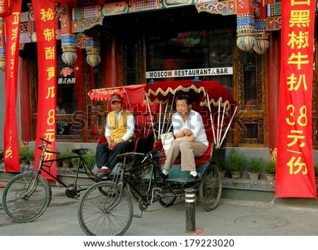 BEIJING - MAY 5, 2005:   Two pedicab drivers in their taxis waiting for fares in front of a restaurant & bar at the Shi Sa Hai Hutong - stock photo