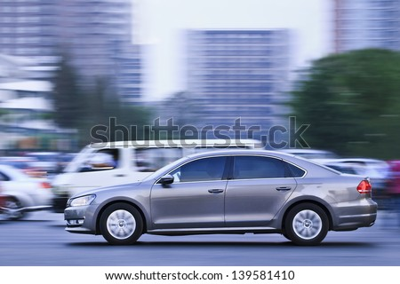 BEIJING-MAY 24. Volkswagen Passat B7 downtown at dusk. Passat is a large family car marketed through six design generations since 1973. It is manufactured in VW Nanjing factory. Beijing, May 24, 2013. - stock photo