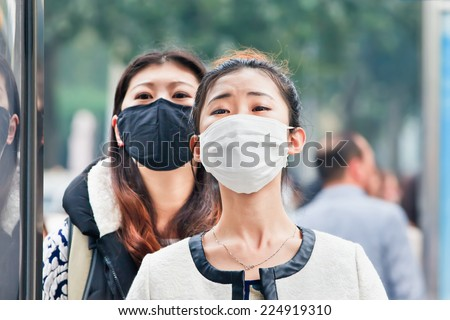 BEIJING-OCT. 19, 2014. Chinese girls with a face mask. Beijing raised its smog alert to orange because the air quality is a health threat. Face masks, once a rarity in Beijing, have now become common. - stock photo