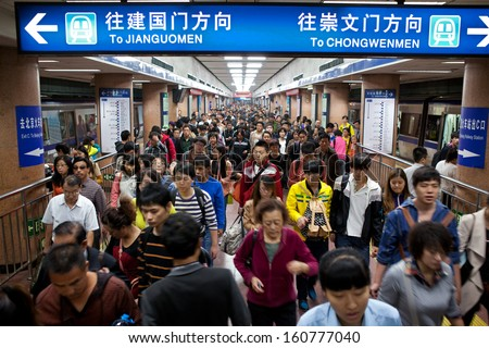BEIJING-OCT 4: Passengers crowd a subway station during National Day holiday on Oct. 4,2013 in Beijing, China. Beijing's 14 subway lines carry over 8.5 million passengers on an average weekday.  - stock photo
