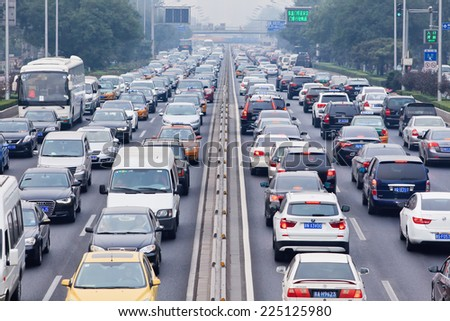 BEIJING-OCT. 19, 2014. Traffic jam in smog covered city. Beijing smog alert went to orange, means hazardous, mainly caused by exhaust emission of five million cars and coal burning in close regions.  - stock photo