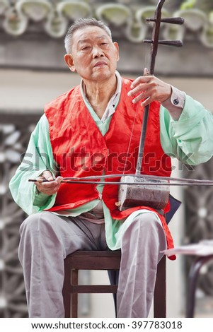 BEIJING-SEPT. 29, 2010. Old man plays an erhu, two-stringed bowed fiddle. The Erhu is an ancient Asian instrument, brought to China during the Han dynasty (140 B.C.) by members of the huqin family.