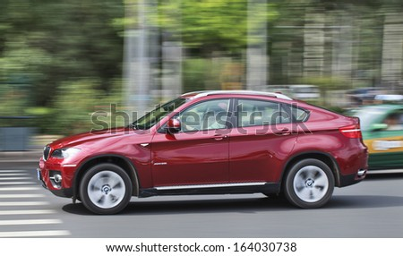 BEIJING-SEPT. 20. Red BMW X6 on the road. Global and upcoming Chinese automakers are scrambling to cash in on the explosive popularity of sport utility vehicles in China. Beijing, Sept. 20, 2013. - stock photo
