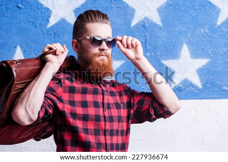 Being cool is simple thing. Handsome young bearded man adjusting his sunglasses and holding a suitcase on his shoulder while standing against American flag - stock photo