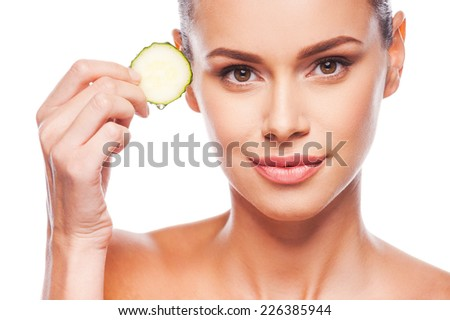 Being fresh is simple deal. Close-up of beautiful young shirtless woman holding slice of cucumber and looking at camera while standing against white background - stock photo