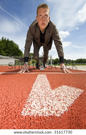 Being number one in business - businessman in the starting blocks on a running track in the first lane - stock photo
