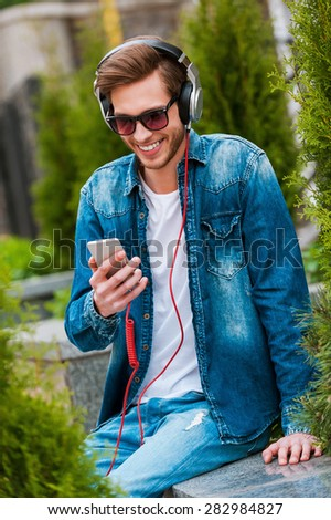 Being on my own wave. Happy young man in headphones holding mobile phone and smiling while sitting outdoors