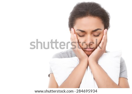 Being sleepy. Young attractive woman backing up her head with hands and embracing white pillow on isolated background - stock photo
