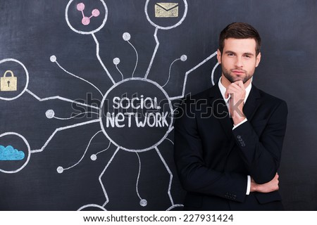 Being social active person. Handsome young man holding hand on chin and looking at camera while standing against social network chalk drawing on blackboard - stock photo
