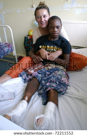 BEIRA, MOZAMBIQUE - CIRCA JULY 2010: Swiss woman Barbara Hofmann in a hospital with an unidentified child wounded in the legs circa July 2010 in Beira, Mozambique. Barbara, after seeing the reality of war helps children orphaned by it.