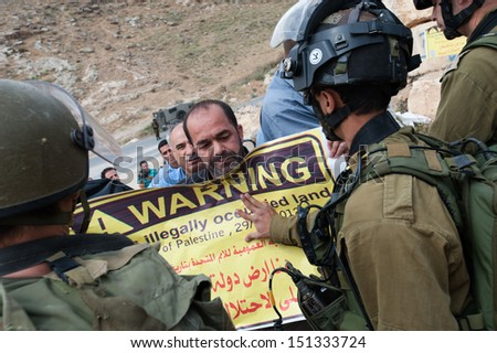 "BEIT SAHOUR, PALESTINIAN TERRITORY - MAY 12: Israeli soldiers push a Palestinian with a sign saying, ""Warning: This is illegally occupied land"" during a protest in Beit Sahour, West Bank, May 12, 2013 - stock photo"
