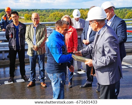 Belarus, Bobruisk District, September 9, 2015: Officials present a certificate and a monetary award to the best construction worker