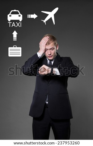 Belated man looking on the wristwatch planning way to airport - stock photo