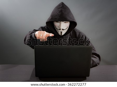 Belchatow, Poland - December 06, 2015: Man wearing Vendetta mask - symbol for the online hacktivist group Anonymous. Black background.