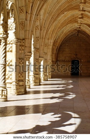 BELEM, PORTUGAL - SEPTEMBER 18, 2012: First floor arcade of the Jeronimos Monastery, with filigreed shadows on floor from the arches opening on the courtyard