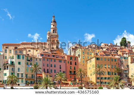 Belfry among colorful houses under blue sky in old town of Menton, France.