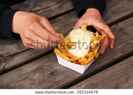 Belgian pommes frites. Hands with a tray of Belgian fries and mayonnaise on top. - stock photo