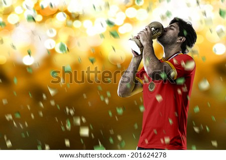 belgian soccer player, celebrating the championship with a trophy in his hand. On a yellow lights background. - stock photo