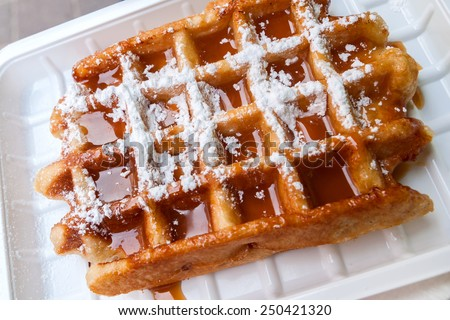 Belgian waffle with caramel syrup and powdered sugar - stock photo