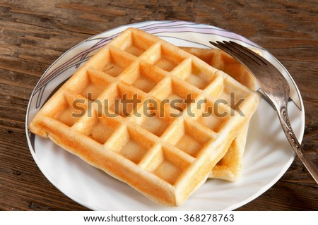 Belgian waffles on a plate on a wooden brown background