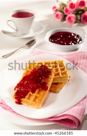 Belgian waffles, red fruits jam and tea breakfast composition