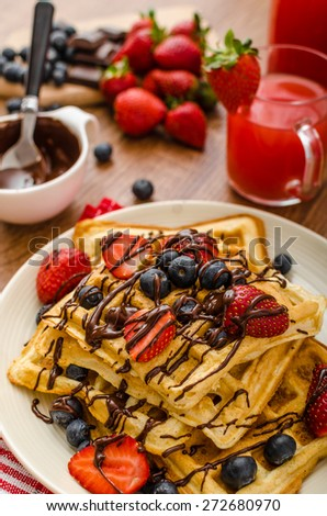 Belgian waffles with blueberries, strawberries covered with chocolate - stock photo