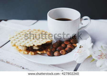 Belgian waffles with peanut butter, hazelnuts on a wooden background. Delicious breakfast with espresso. Horizontal view - stock photo