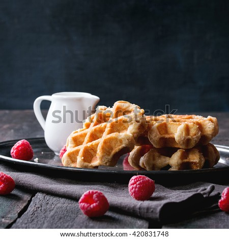 Belgian waffles with raspberries, served with jug of milk on vintage metal tray with textile napkin over old wooden table. Dark rustic style. Square image - stock photo
