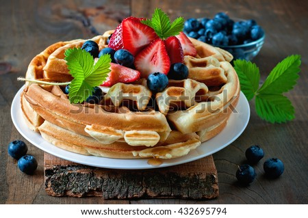 Belgian waffles with strawberries, blueberries and syrup, homemade healthy breakfast, toned image, selective focus - stock photo