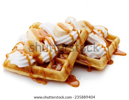 Belgian waffles with whipped cream, caramel sauce and bananas isolated on white background - stock photo